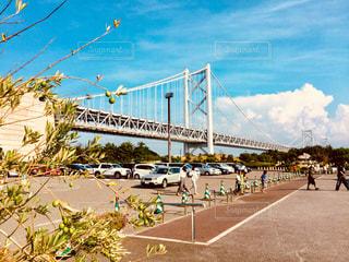 橋の前を歩く人々のグループ - No.909661