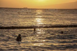 海で夕日を待つ男の写真・画像素材[1029980]