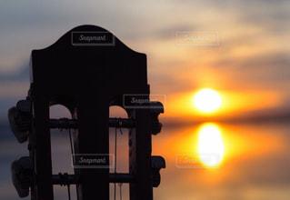 朝陽とギターでの写真・画像素材[911269]