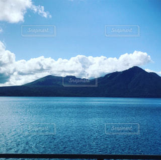水の体の前に雲の写真・画像素材[906502]