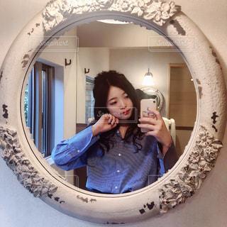 カメラにポーズ鏡の前に立っている女性の写真・画像素材[1167555]