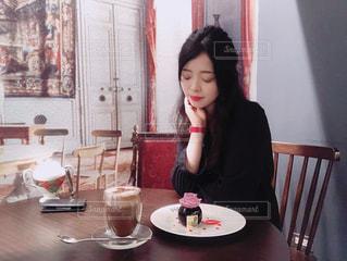 テーブルに座っている女性の写真・画像素材[1186656]