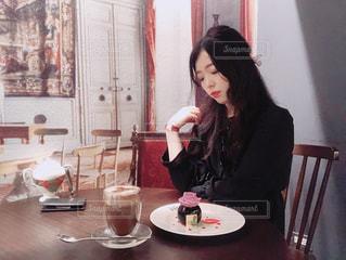 テーブルに座っている女性の写真・画像素材[1186657]