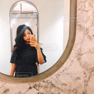 カメラにポーズ鏡の前に立っている女性の写真・画像素材[1199406]