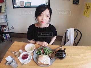 食品のプレートをテーブルに座っている女性の写真・画像素材[1235524]