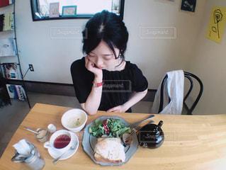 食物と一緒にテーブルに座っている女性の写真・画像素材[1235528]