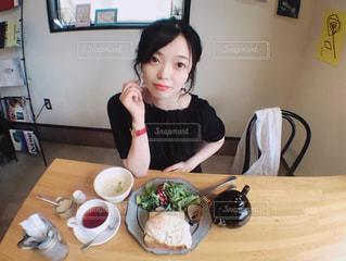 食事のテーブルに座っている女性の写真・画像素材[1235529]