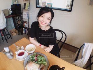 食品のプレートをテーブルに座っている女性の写真・画像素材[1235546]