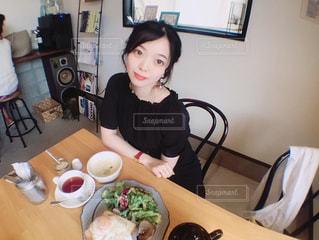 食品のプレートをテーブルに座っている女性の写真・画像素材[1235547]
