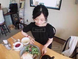 食品のプレートをテーブルに座っている女性の写真・画像素材[1235548]