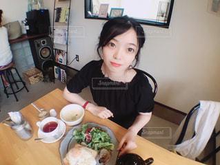 食品のプレートをテーブルに座っている女性の写真・画像素材[1235550]