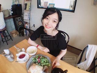 食品のプレートをテーブルに座っている女性の写真・画像素材[1235551]