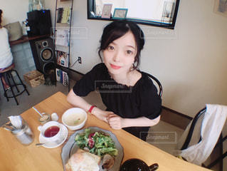 食品のプレートをテーブルに座っている女性の写真・画像素材[1235552]