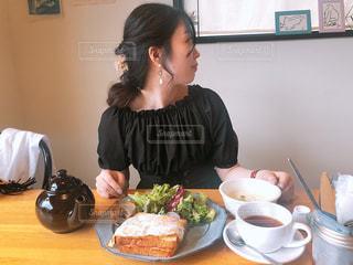 食品のプレートをテーブルに座っている女性の写真・画像素材[1235563]