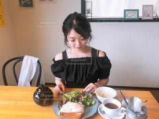 食品のプレートをテーブルに座っている女性の写真・画像素材[1235565]