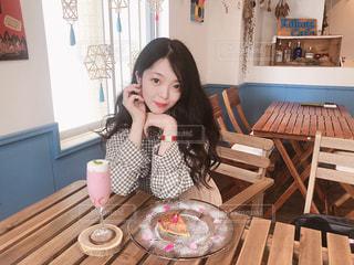 木製のテーブルに座っている女性の写真・画像素材[1261436]
