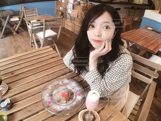 木製のテーブルに座っている少女の写真・画像素材[1264826]