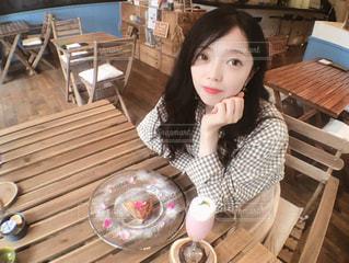 木製のテーブルに座っている女の子の写真・画像素材[1264828]