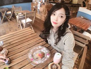 木製のテーブルに座っている女性の写真・画像素材[1264829]