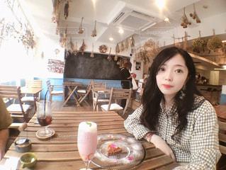 レストランのテーブルに座っている女性の写真・画像素材[1264836]