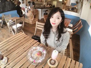 テーブルの上に座っている女性の写真・画像素材[1264840]
