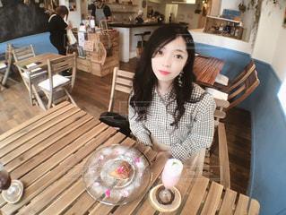 木製のテーブルに座っている女性の写真・画像素材[1264842]