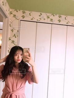 カメラにポーズ鏡の前に立っている女性の写真・画像素材[1268368]