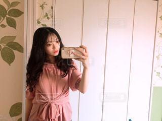 カメラにポーズ鏡の前に立っている人の写真・画像素材[1268369]
