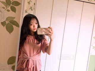 カメラにポーズ鏡の前に立っている女性の写真・画像素材[1268370]