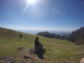 草で覆われた丘の上に立っている人の写真・画像素材[1268418]