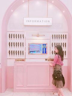 鏡の前に立っているピンクのドレスの女の子の写真・画像素材[1268421]