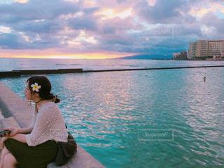 水の体の横に座っている人の写真・画像素材[1268429]