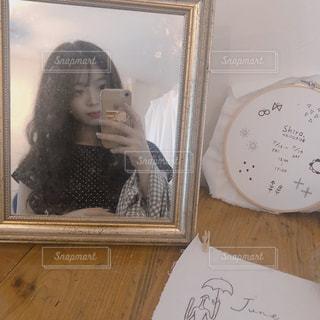 カメラにポーズを鏡の前に座っている女性の写真・画像素材[1272961]