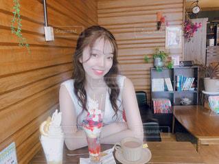 テーブルの上に座っている女性の写真・画像素材[1285529]