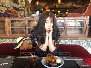 食事のテーブルに座っている女性の写真・画像素材[1297681]