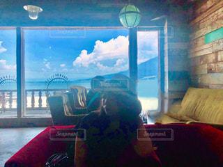 窓の前に座っている人の写真・画像素材[1297683]