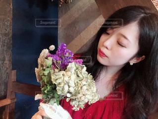 花の花瓶とテーブルに座っている女性の写真・画像素材[1324878]