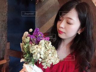 花の花瓶とテーブルに座っている女性の写真・画像素材[1324880]