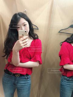 カメラにポーズ鏡の前に立っている女性の写真・画像素材[1324887]
