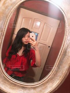 カメラにポーズ鏡の前に立っている女性の写真・画像素材[1324889]