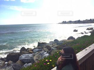 海の近くの岩の上に座って男の写真・画像素材[1324895]