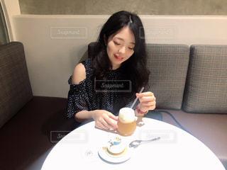一杯のコーヒーをテーブルに座っている女性の写真・画像素材[1324924]