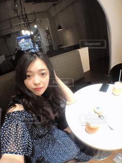 カメラにポーズのテーブルに座っている女性の写真・画像素材[1324925]