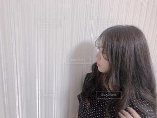 カーテンの前に立っている女性の写真・画像素材[1328351]