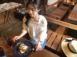 木製のテーブルに座っている女の子の写真・画像素材[1330035]