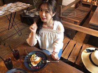 木製のテーブルに座っている女の子の写真・画像素材[1330036]