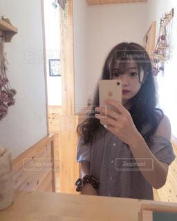 カメラにポーズ鏡の前に立っている女性の写真・画像素材[1360457]