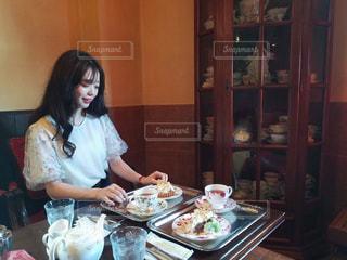 食品のプレートをテーブルに座っている女性の写真・画像素材[1408293]