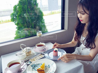 食品のプレートをテーブルに座っている女性の写真・画像素材[1408299]