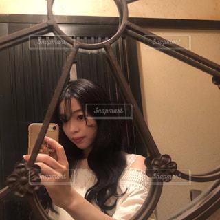 カメラにポーズ鏡の前に立っている女性の写真・画像素材[1451449]